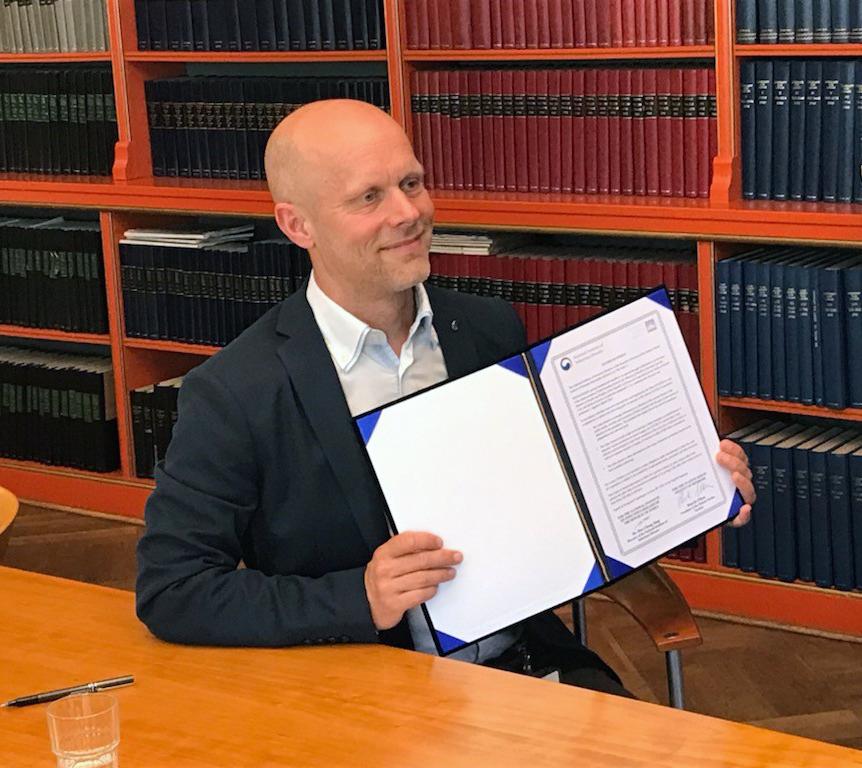 Administrerende direktør på SSI, Henrik Ullum holder her aftalen op for webkameraet.