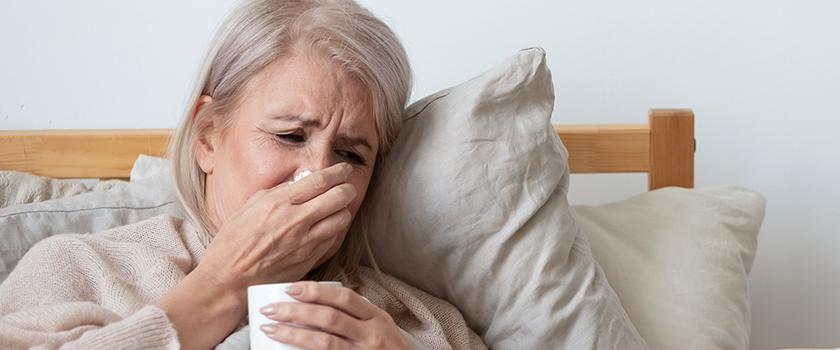 Kvinde ligger i sengen med influenza
