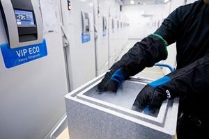 Frysere til opbevaring af vacciner.  Mand står med en frostpakke.